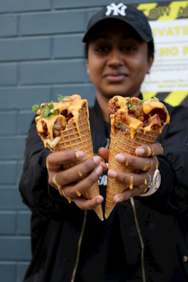 Girl holding two fried chicken waffle cones